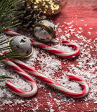 Christmas decoration with snow and candy cane on a red wooden background close up. Christmas decoration with snow and candy cane on red wooden background close Royalty Free Stock Photos