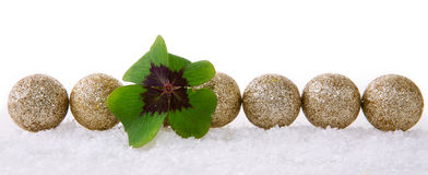 Christmas decoration with snow and cloverleaf. Christmas decoration with snow isolated on white background.Lucky symbols: four-leaf clover and balls . Green Stock Images