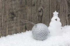 Christmas decoration on snow. Christmas tree figurine with silver ball on snow against old wooden boards Stock Photo