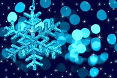 Christmas decoration snowflake on defocused lights. Christmas decoration snowflake  on defocused lights and stars background / blue toned Stock Photos