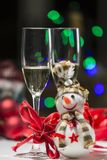 Christmas decoration with snowman colored lights, champagne glas. Composition for Christmas with balls, a snowman, some red ribbons, colored lights and two stock images