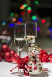 Christmas decoration with snowman colored lights, champagne glas. Composition for Christmas with balls, a snowman, some red ribbons, colored lights and two royalty free stock photos