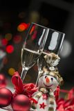 Christmas decoration with snowman colored lights, champagne glas. Composition for Christmas with balls, a snowman, some red ribbons, colored lights and two stock photos