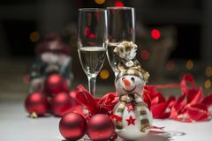Christmas decoration with snowman colored lights, champagne glas. Composition for Christmas with balls, a snowman, some red ribbons, colored lights and two stock image