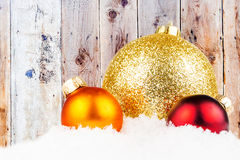 Christmas decoration on snowy surface and wooden laths Royalty Free Stock Photo