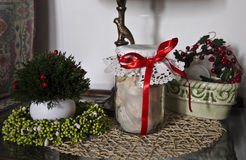 Christmas decoration. Some cookie jar with red ribbon and vase with garland inside Royalty Free Stock Image