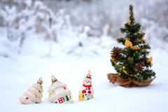 Christmas decoration. Some Christmas toys in the snow near a Christmas tree stock image