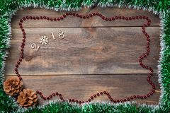 Christmas decoration spangle frame with cones and decorative wooden figures 2018 on blank wooden background. Can be used as a temp Royalty Free Stock Photos