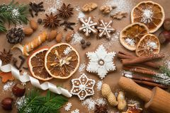 Christmas decoration with spices and cookies in the shape of snowflakes on dark brown paper background. Top view. stock photos