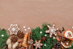 Christmas decoration with spices and cookies in the shape of snowflakes on dark brown paper background. Top view. royalty free stock photography