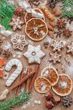 Christmas decoration with spices and cookies in the shape of snowflakes on dark brown paper background. Top view. stock image