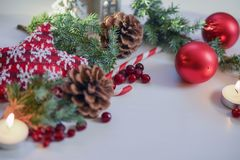 Christmas 2018 decoration for table,Christmas tree red balls, burning candle with fir branch and candle on wooden background Stock Photography