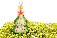 Christmas decoration toy fir-tree on the golden bead isolated Stock Images