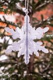 Christmas decoration with a toy in the shape of silver snowflake, selective focus. Image with copy space. royalty free stock photography