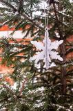 Christmas decoration with a toy in the shape of silver snowflake, selective focus. Image with copy space. Christmas postcard stock photo