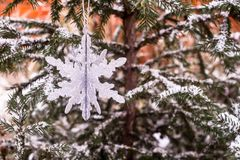 Christmas decoration with a toy in the shape of silver snowflake, selective focus. Image with copy space. Christmas postcard stock image