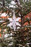 Christmas decoration with a toy in the shape of silver snowflake, selective focus. Image with copy space. royalty free stock images