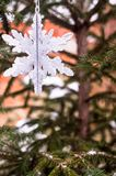 Christmas decoration with a toy in the shape of silver snowflake, selective focus. Image with copy space. stock photo