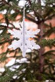 Christmas decoration with a toy in the shape of silver snowflake, selective focus. Image with copy space. royalty free stock photo