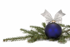 Christmas decoration with tree branch. Christmas blue bauble with ornamental ribbon (bow) arranged on Common Fir (Abies alba) twig on white background Stock Photo
