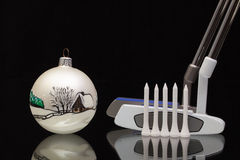 Christmas decoration and two golf putters Stock Photos