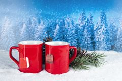 Christmas decoration with two red cups of hot tea on a backgroun Stock Photo