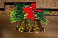 Christmas decoration, two shiny golden bells with fir branch Stock Photos