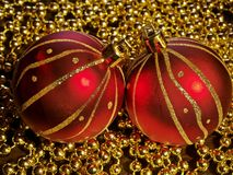 Christmas decoration. Two christmas tree balls over golden beads Royalty Free Stock Image