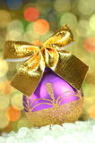 Christmas decoration, violet Christmas ball with golden bow Royalty Free Stock Photos