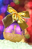 Christmas decoration, violet Christmas ball with golden bow Stock Photography