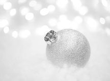 Christmas Decoration with White Ball in the Snow on the Blurred Background with Lights. Greeting Card Stock Images