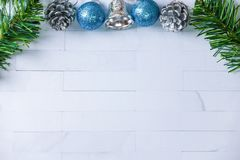 Christmas decoration on white brick with silver bell, fir branch stock photo