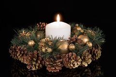 Christmas decoration with a white candle and pine apples at a black background Stock Photo