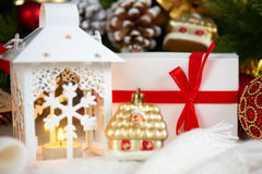 Christmas decoration on white fur with fir tree branch closeup, gifts, xmas ball, cone and other object on dark background with li Royalty Free Stock Image