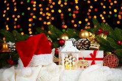 Christmas decoration on white fur with fir tree branch closeup, gifts, xmas ball, cone and other object on dark background with li Stock Photos
