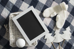 Christmas decoration with white knitted mittens wooden frame and white basket on the checkered background Stock Image