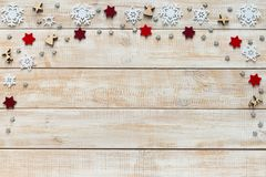 Christmas decoration with white snowflakes and red stars. Christmas decoration with white snowflakes, red stars and wooden figures on a wooden background Royalty Free Stock Images