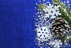 Christmas decoration.White snowflakes and snowy fir tree branch and pine cone on blue background with copyspace. Stock Photos