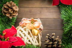 Christmas decoration with wicker ball, pine cones and poinsettia Stock Photos