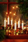 Christmas decoration on window sill. Christmas arrangement of electric candles on a wooden window sill creating warm homely atmosphere Stock Photography