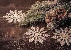 Christmas decoration on wooden background. The snowy fir tree  with pine cones and shiny snowflakes on a  wooden background Royalty Free Stock Image