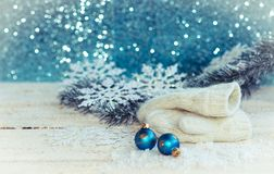 Christmas decoration on wooden background. White mittens with snowflakes, fir branch and balls on a wooden background Stock Photography
