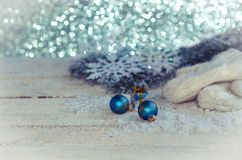 Christmas decoration on wooden background. White mittens with snowflakes, fir branch and balls on a wooden background Royalty Free Stock Image