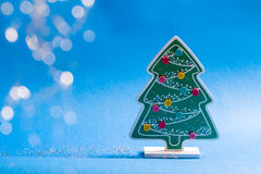 Christmas decoration. Wooden figurine of christmas tree with glued coloured buttons and glow stars and balls Stock Photos
