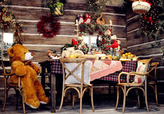 Christmas decoration. A wooden house full of Christmas decoration ,and a lonely bear sitting on the chair, celebrating Christmas alone stock photo