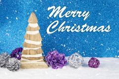 Christmas decoration with wooden pinewood figurine, baubles and pines  on a background with text in English `Merry Christmas`. On white snow and shiny blue Royalty Free Stock Photos