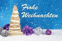 Christmas decoration with wooden pinewood figurine, baubles and pines  on a background with text in German `Frohe Weihnachten ` Stock Photography