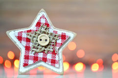 Christmas decoration: Wooden star against Christmas lights Royalty Free Stock Photo