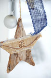Christmas decoration with a wooden star and blue ribbon hanging Royalty Free Stock Photos
