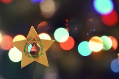 Christmas decoration wooden star. Holiday wooden star with a bell on the background of Christmas lights Stock Image